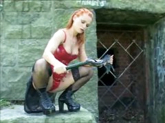 Girl in leather with a flogger outdoors
